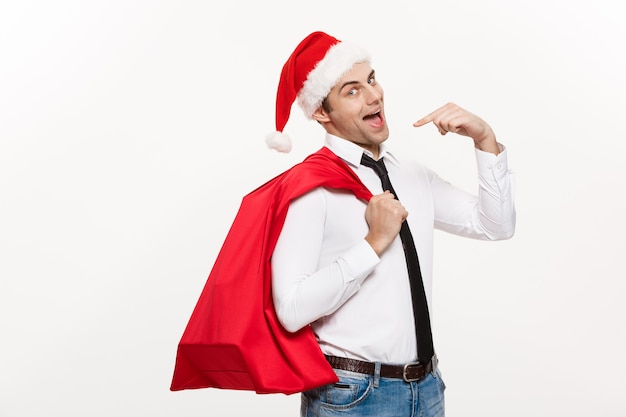 De knappe bedrijfsmens viert vrolijke kerstmis die santahoed met de rode grote zak van de kerstman draagt.