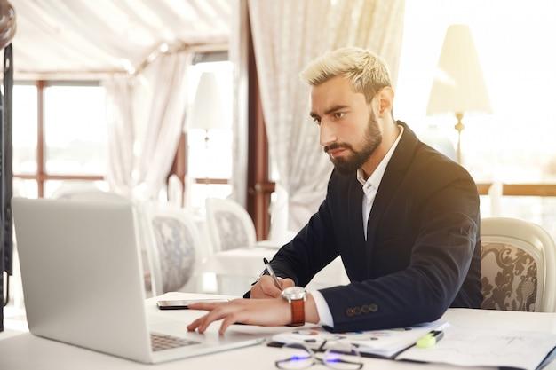 De knappe bedrijfsmens werkt aan laptop bij het restaurant