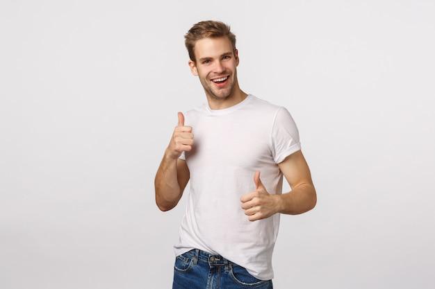 De knappe blonde kerel met blauwe ogen en het witte t-shirt geven beduimelt omhoog
