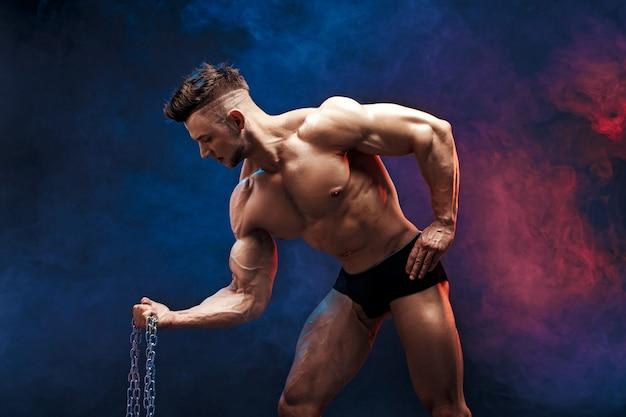 De knappe bodybuilder die van de machts atletische mens oefeningen met ketting doen. geschiktheids gespierd lichaam op donkere rokerige achtergrond. perfecte reu. geweldige bodybuilder, die zich voordeed.