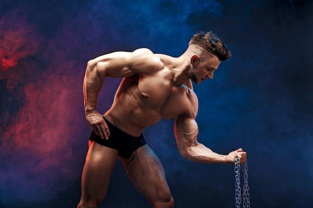 De knappe bodybuilder die van de machts atletische mens oefeningen met ketting doen. geschiktheids gespierd lichaam op donkere rokerige achtergrond.
