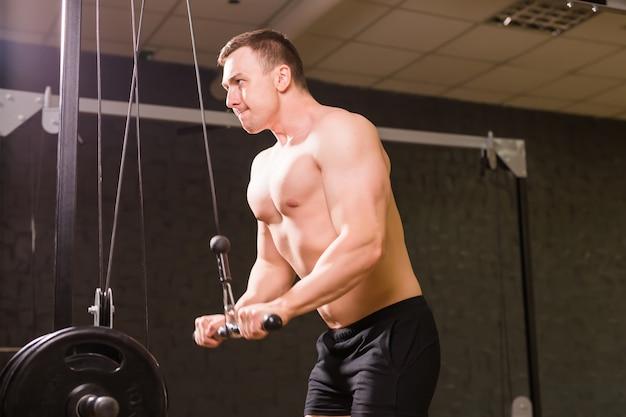 De knappe bodybuilder werkt oefening in gymnastiek uit