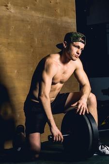 De knappe bodybuilderkerel treft voorbereidingen om oefeningen met barbell in een gymnastiek te doen