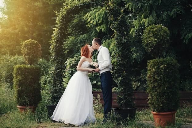 De knappe bruidegom houdt de hand van de bruid dichtbij groene bloemoverwelfde galerij