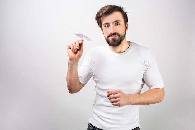 De knappe en gelukkige mens in wit overhemd bevindt zich dichtbij de muur en houdt een papieren vliegtuigje. hij is klaar om het te lanceren. geïsoleerd op witte muur.