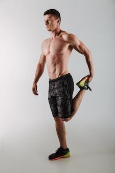 De knappe geconcentreerde jonge sportman maakt rekoefeningen