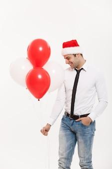 De knappe gelukkige bedrijfsmens die met rode ballon lopen viert vrolijke kerstmis die santahoed draagt.