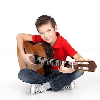 De knappe gelukkige jongen speelt op geïsoleerde akoestische gitaar -
