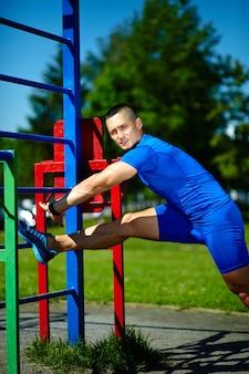 De knappe gezonde gelukkige mannelijke mens die van de srtongatleet bij het stadspark uitoefenen - geschiktheidsconcepten op een mooie de zomerdag op rekstok