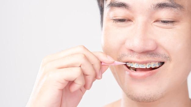 De knappe glimlach jonge man gebruikt tandzijde