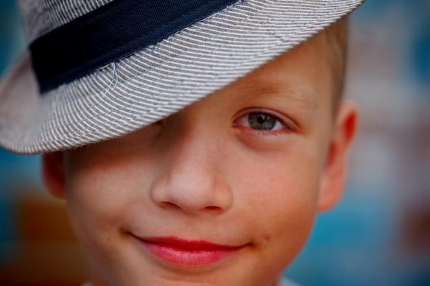 De knappe glimlachende jongen van het close-upportret in een de zomerhoed