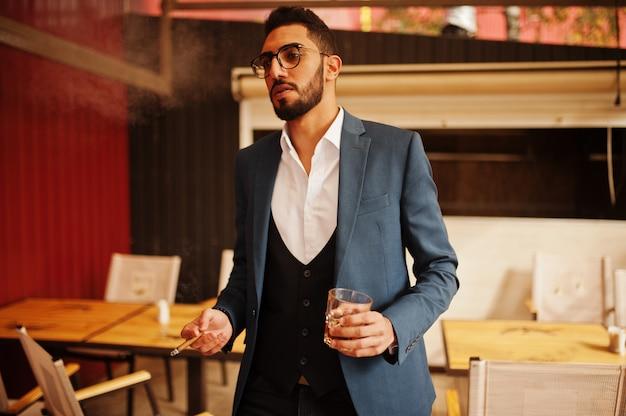 De knappe goed geklede arabische sigaar van de mensenrook met glas whisky bij balkon van bar.