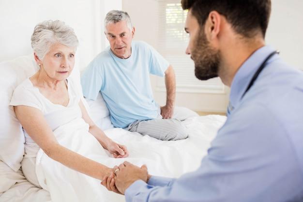 De knappe hand van de verpleegstersholding van rijpe vrouw thuis
