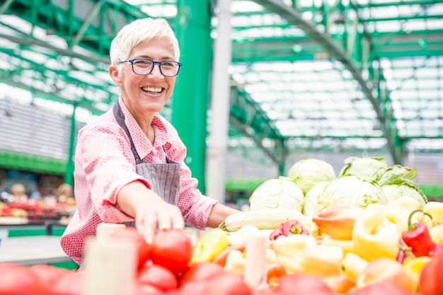 De knappe hogere vrouw die glazen draagt verkoopt peper op markt