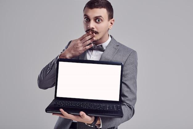 De knappe jonge arabische zakenman met snor in grijs kostuum houdt laptop