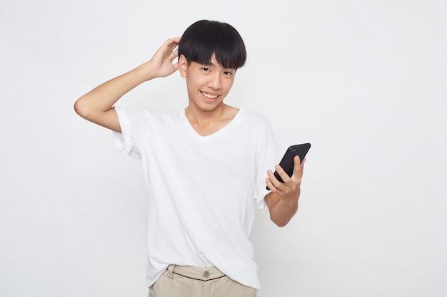 De knappe jonge aziatische mens die een telefoon toont aan lege ruimte geïsoleerde witte oppervlakte