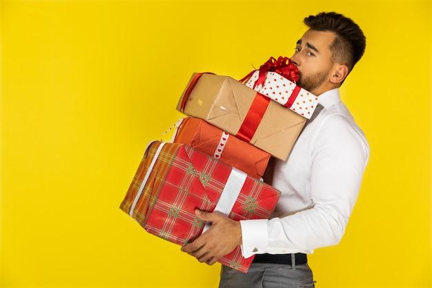 De knappe jonge europese kerel houdt zwaar ingepakte giften en cadeaus