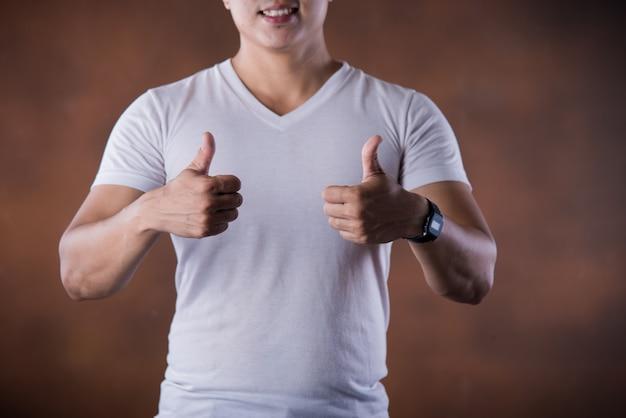 De knappe jonge glimlachende mens die van het portret duimen op het richten van vingers geeft