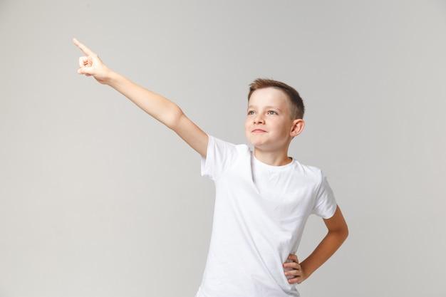 De knappe jonge jongen bevindt zich in de houding van een held en steekt zijn hand op. motivator