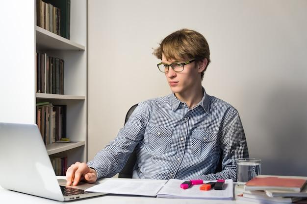 De knappe jonge mannelijke persoon werkt met boeken en laptop aan huistaak