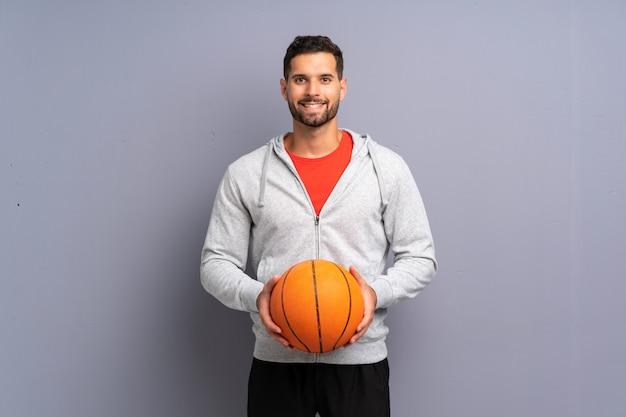 De knappe jonge mens die van de basketbalspeler veel glimlacht