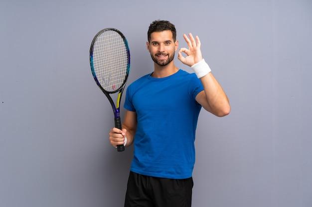 De knappe jonge mens die van de tennisspeler ok teken met vingers tonen