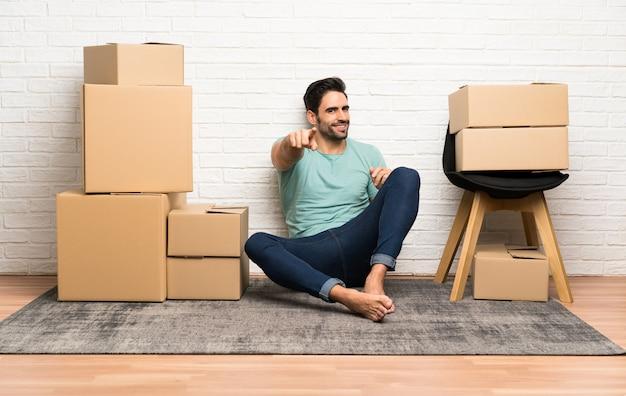 De knappe jonge mens die zich in nieuw huis onder dozen bewegen richt vinger op u