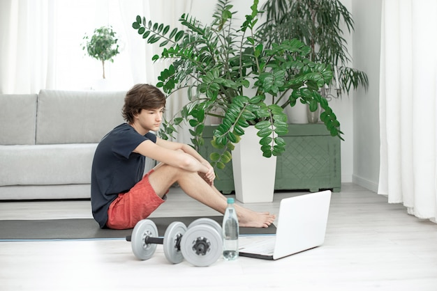 De knappe jonge mens doet thuis sporten en let op online opleiding