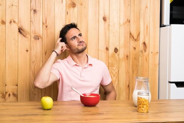 De knappe jonge mens in een keuken die ontbijt hebben die twijfels hebben en met verwart gezichtsuitdrukking