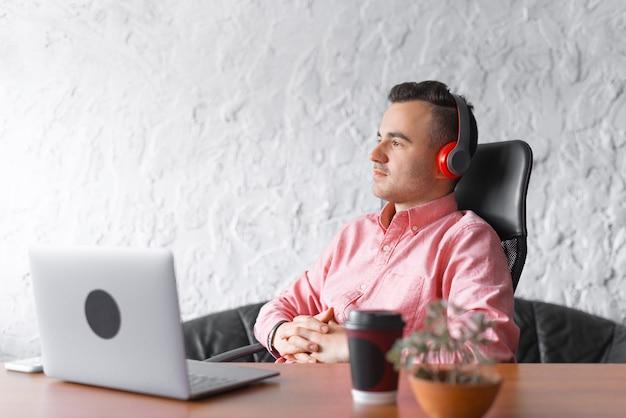 De knappe jonge mens luistert aan audioboek of muziek in hoofdtelefoons