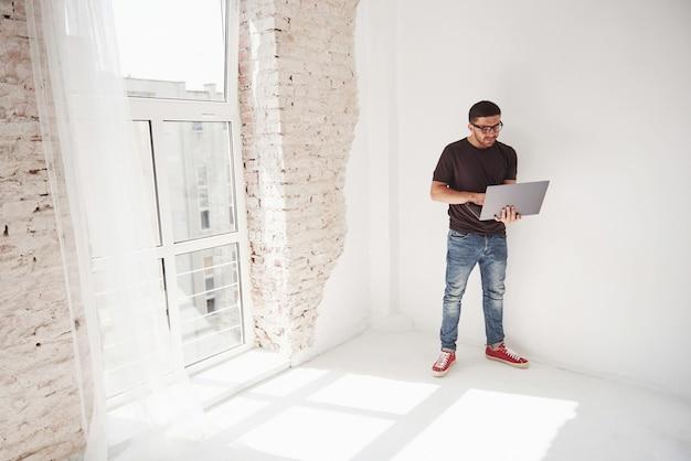 De knappe jonge mens met laptop en controleert zijn tijdschema op wit