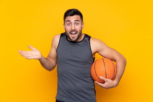 De knappe jonge mens van de basketbalspeler over geïsoleerde witte muur met geschokte gelaatsuitdrukking