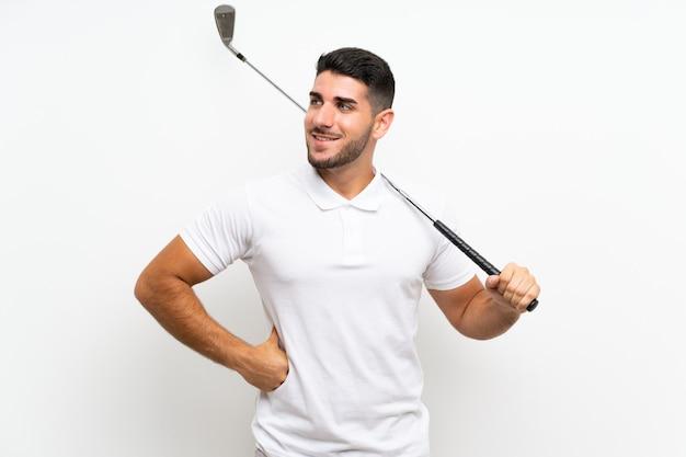 De knappe jonge mens van de golfspelerspeler over geïsoleerd wit die omhoog terwijl het glimlachen kijken