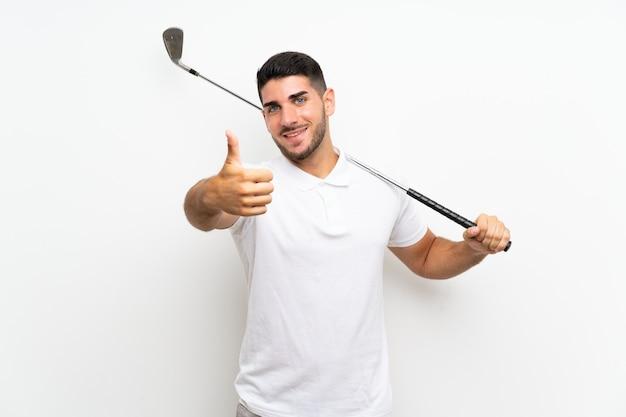 De knappe jonge mens van de golfspelerspeler over geïsoleerd wit met omhoog duimen omdat iets goeds is gebeurd