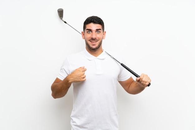 De knappe jonge mens van de golfspelerspeler over geïsoleerd wit met verrassingsgelaatsuitdrukking