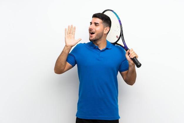 De knappe jonge mens van de tennisspeler over geïsoleerde witte muur die met wijd open mond schreeuwen