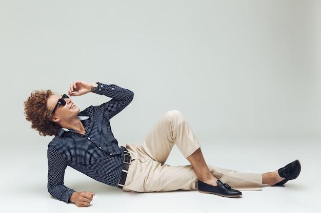 De knappe jonge retro mens gekleed in overhemd ligt op vloer