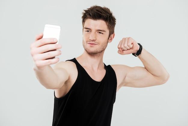 De knappe jonge sportman met telefoon maakt selfie