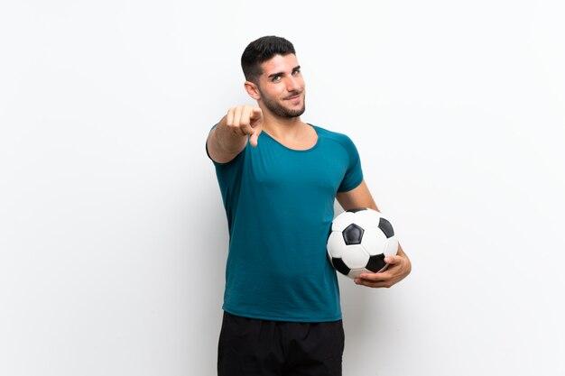 De knappe jonge voetbalstermens over geïsoleerde witte muur richt vinger op u met een zekere uitdrukking