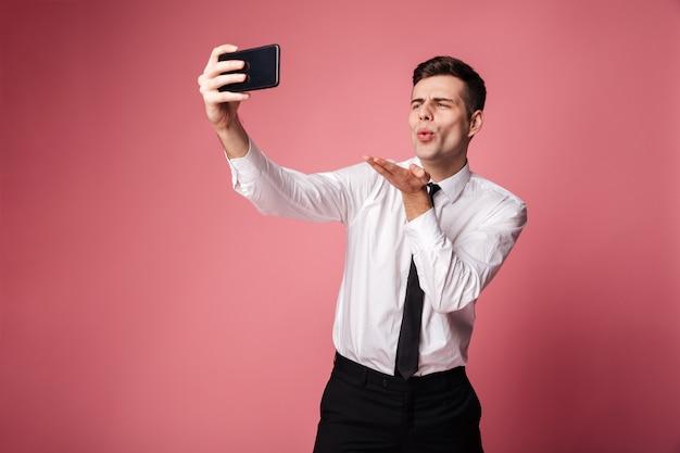 De knappe jonge zakenman maakt selfie door mobiele telefoon blazende kussen.