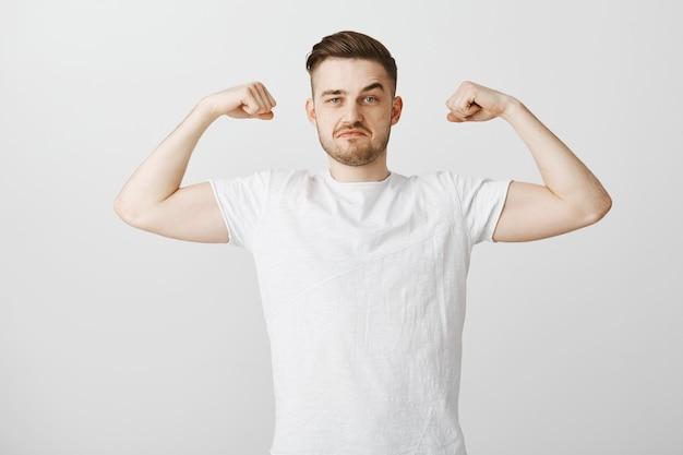 De knappe jongeman pronkt met zijn kracht, buigt spieren en glimlacht trots