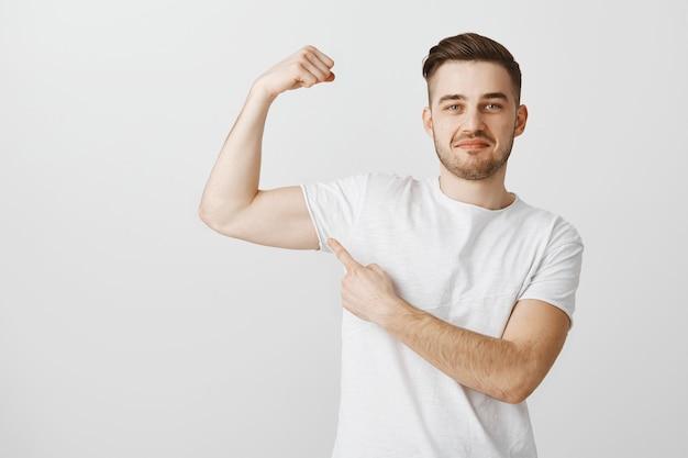 De knappe jongeman pronkt met zijn kracht door naar de sportschool te gaan om te trainen, spieren te buigen en trots te glimlachen