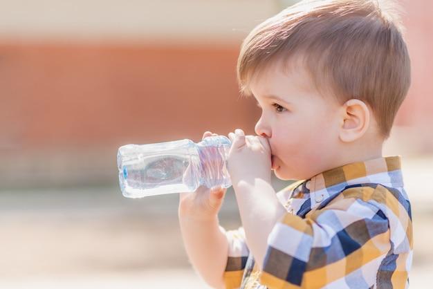 De knappe jongen drinkt duidelijk water buiten van een fles op een zonnige dag