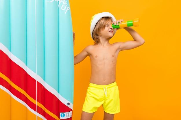 De knappe jongen in zwembroek houdt een rubbermatras, glimlacht en gesticuleert geïsoleerd op oranje achtergrond