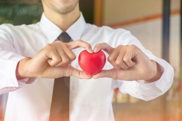 De knappe kelner dient en houdt hart met liefde op valentijnsdag