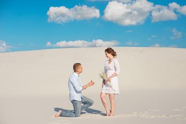 De knappe kerel doet het meisje een huwelijksaanzoek, buigt zijn knie, staand op het zand in de woestijn.