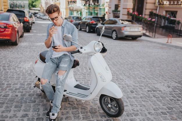 De knappe kerel zit op motorfiets en houdt telefoon in hand