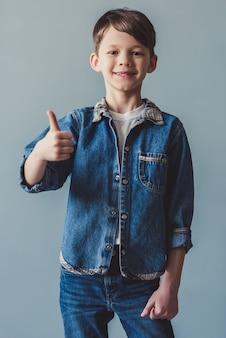De knappe kleine jongen in de kleren van jean toont ok teken.
