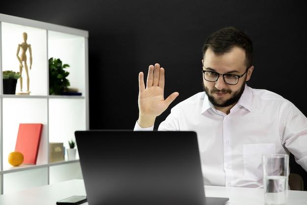 De knappe leraar houdt videoconferentie op laptop, opgeheven hand in groet
