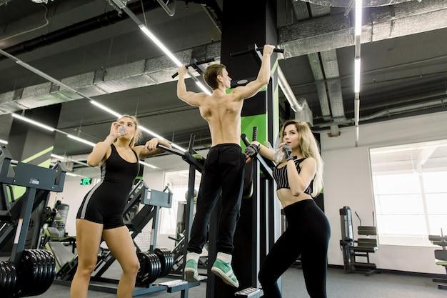 De knappe machts atletische mens opleiding die omhoog achterspieren opvoeren trekt in de gymnastiek uit. sterke bodybuilder traint in de sportschool, traint zijn rug. twee meisjes met waterflessen die zich dichtbij bar bevinden
